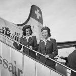 """Erste Swissair DC-4, HB-ILA, die nach einem Flug über den Atlantik mit Captain Otto Heitmanek am 24.11.1946 in Genf landete. Dieser Anlass wurde entsprechend gefeiert und das Flugzeug auf den Namen """"Genève"""" getauft. Zeitgenössische Bildbeschreibung des Swissair-Marketings: """"Stewardessen Pia Goth und Hedwig Hofmann (Taufe HB - ILA DC-4, Genf)"""""""